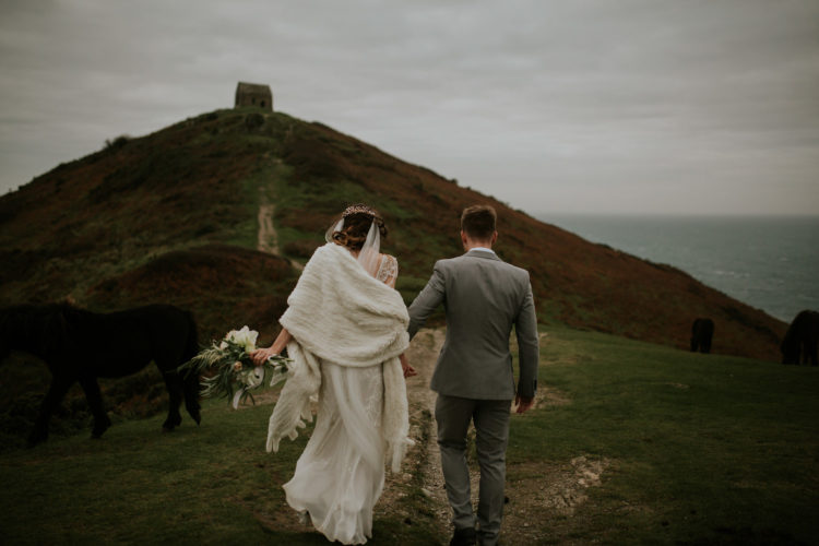 The bride covered up with faux fur for a walk along the coast