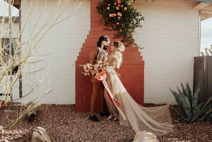The ceremony space was a red brick wall plus greenery and peachy pink blooms