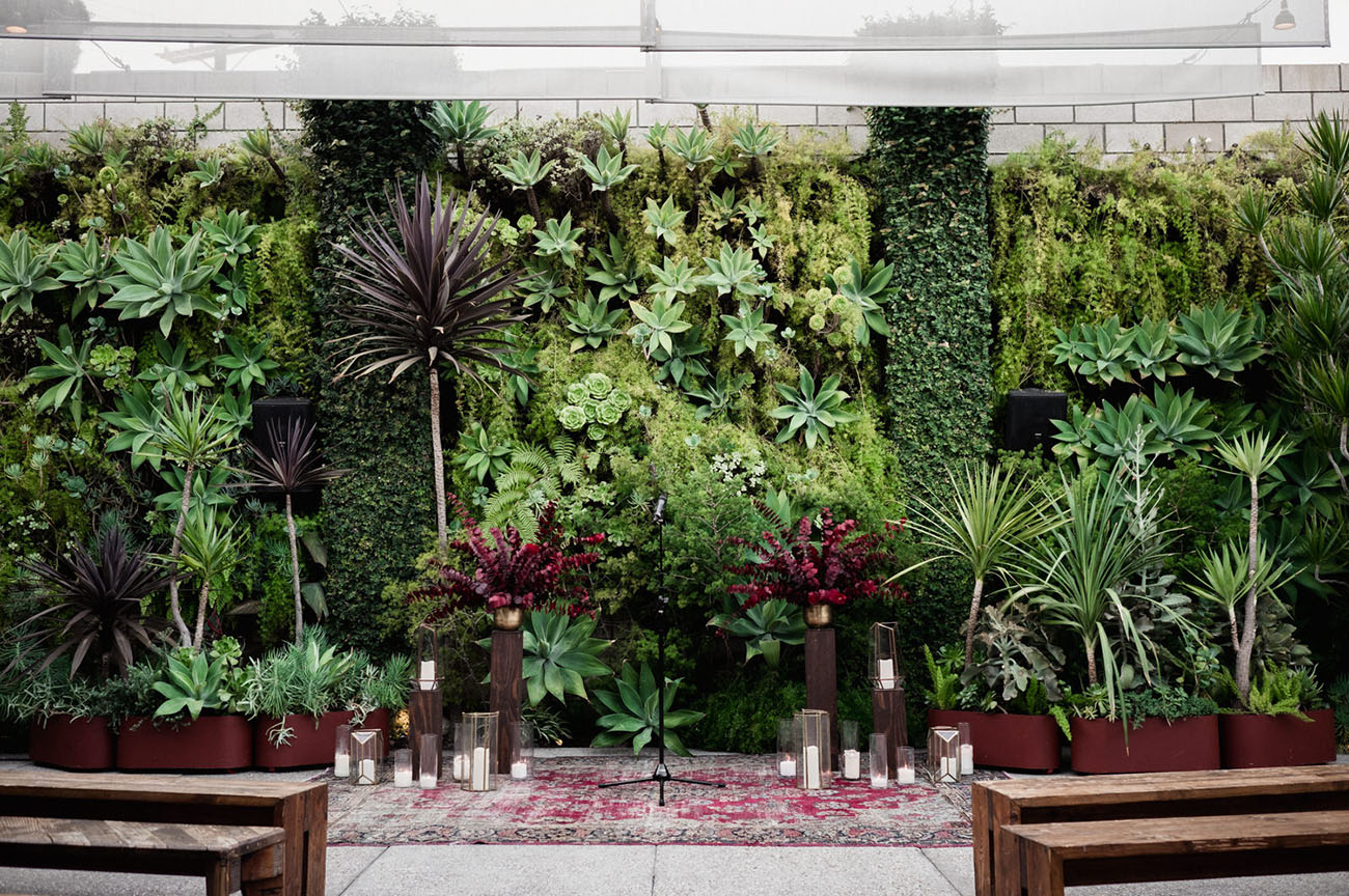The wedding backdrop was done with a living wall of succulents and lush greenery, there were candles and burgundy blooms