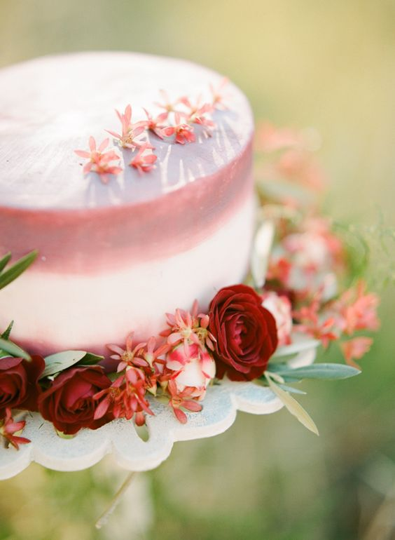 a blush and white ombre cake with burgundy blooms and greenery for a chic and bold look