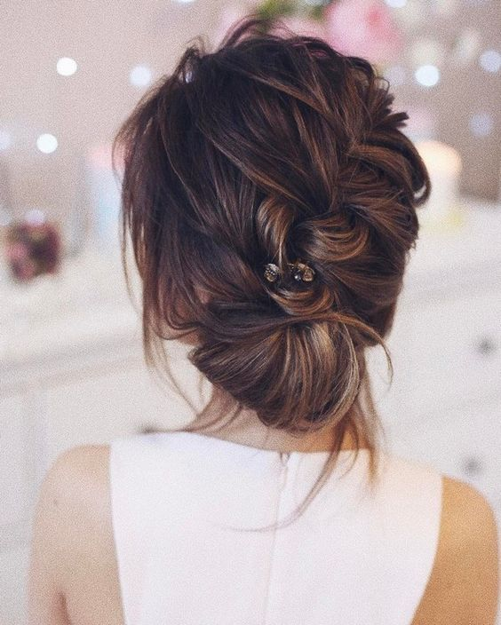 a braided low updo with a volume and some locks plus a rhinestone hairpiece