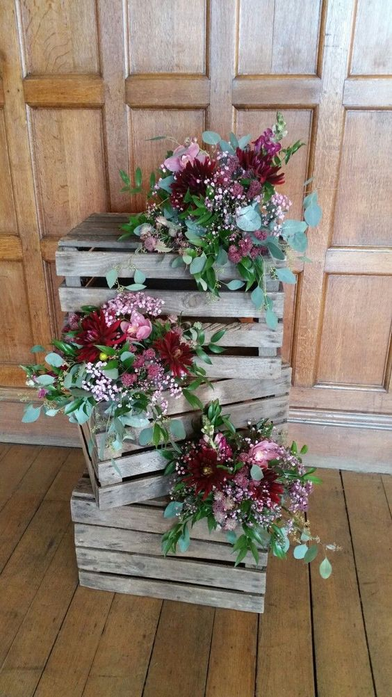 a crate stack with bright blooms and greenery arrangements will be a nice decoration for a rustic wedding