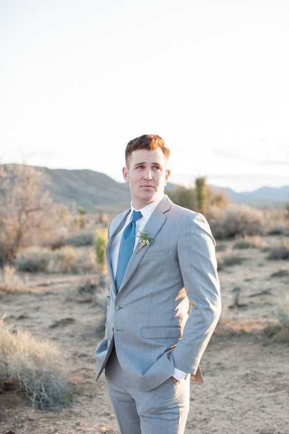a light grey suit with a blue tie and a white shirt for a modern groom's outfit