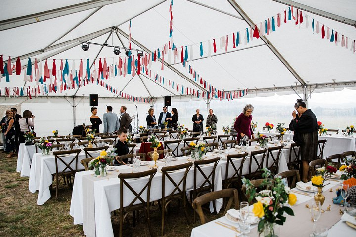 The wedding tent was decorated with colorful bunting and bright floral centerpieces