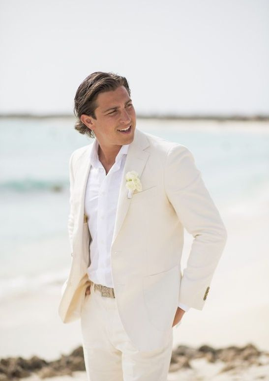 a creamy suit, a white shirt, a white floral boutonniere for a beach groom