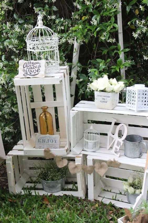 a whitewashed crate combo with bottles, cages, flowers in vases, metal mugs and cans