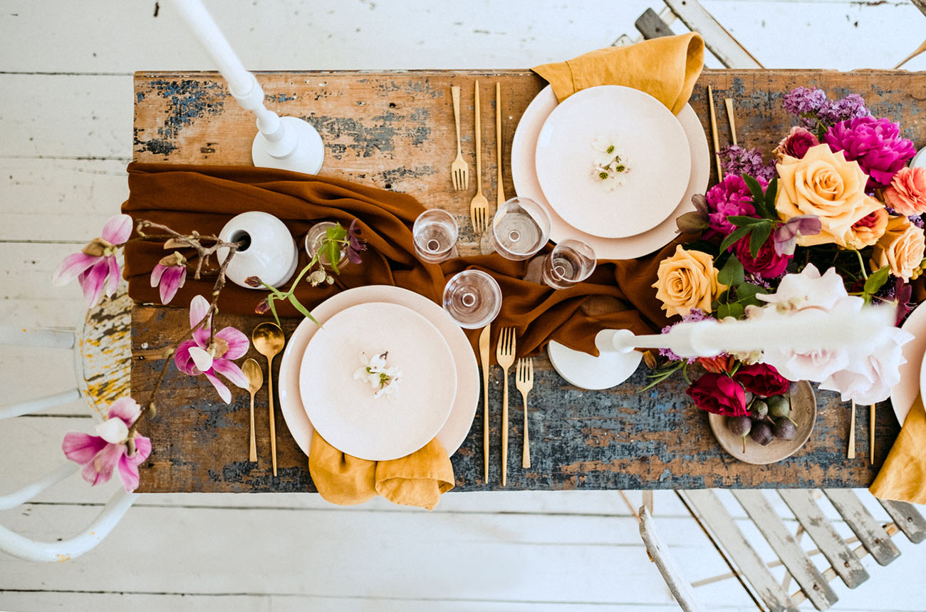 The shabby chic table was done with a rust table runner, mustard napkins, gold cutlery and bright and lush blooms