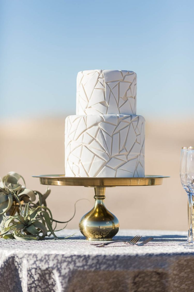 The wedding cake was a white geometric one, presented on a gold stand