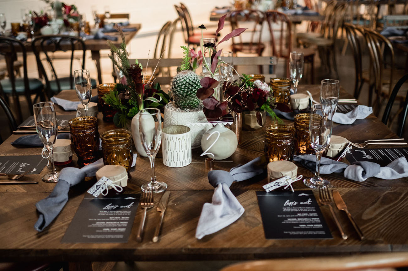 The wedding tablescapes were done with cacti, greenery, dark blooms and hand dyed napkins