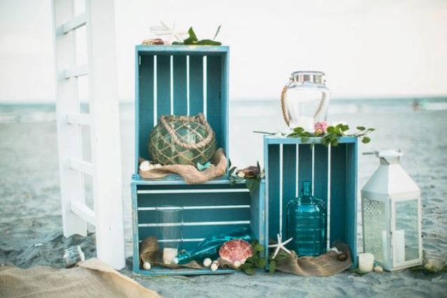 a bright crate combo in turquoise with candle lanterns and bottles, shells and star fish for a beach wedding