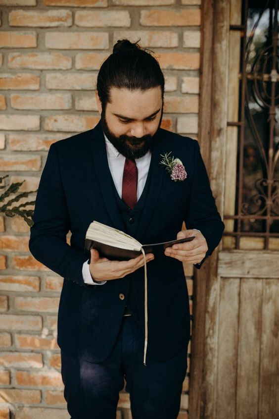a chic groom's look with a three-piece suit, a burgundy tie and a floral boutonniere