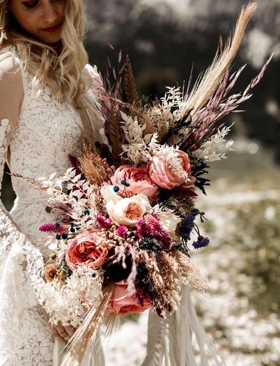 a luxurious boho wedding bouquet with pampas grass, feathers, peonies and berries for a wow effect