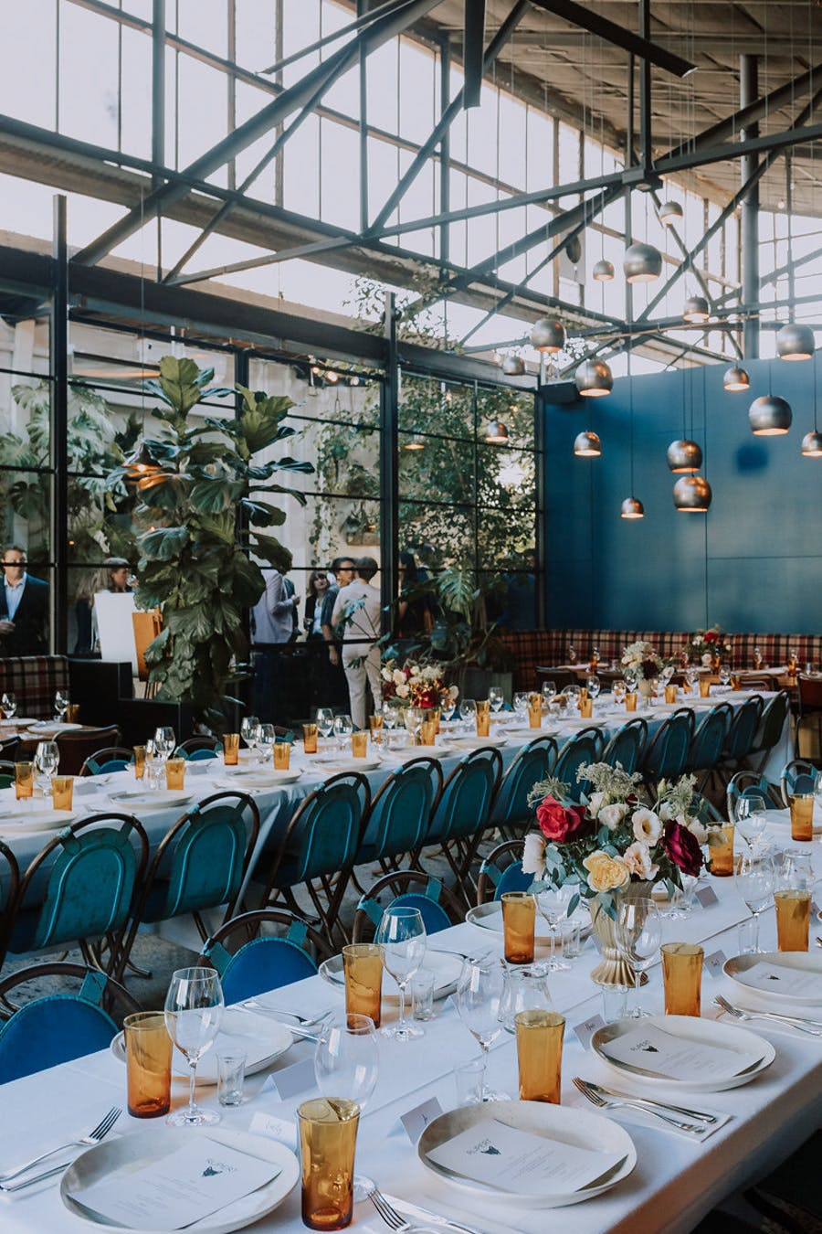 The wedding venue was industrial, with touches of blue and teal and amber glasses plus cute blooms