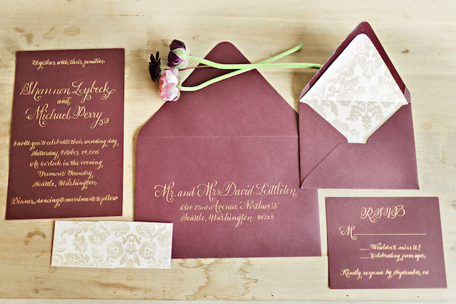 a chic wedding invitation suite in burgundy and with gold calligraphy and botanical prints