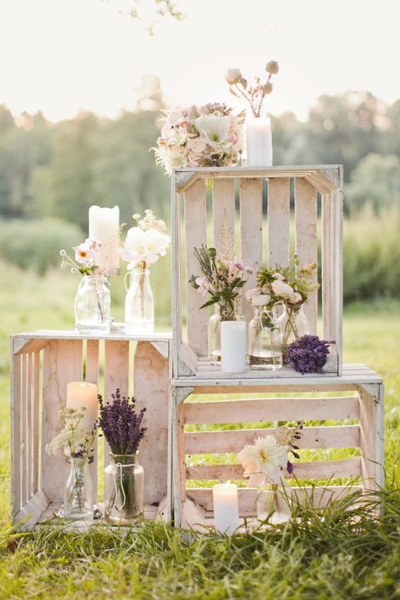 a crate decoration with candles, blooms in jars and vases for an outdoor rustic wedding