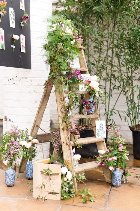 a rustic ladder with greenery and blooms in vases and botanical posters for a rustic wedding