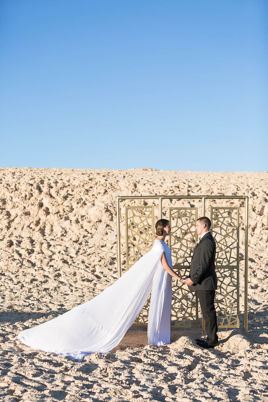 The wedding backdrop was a gold laser cut one placed in the desert