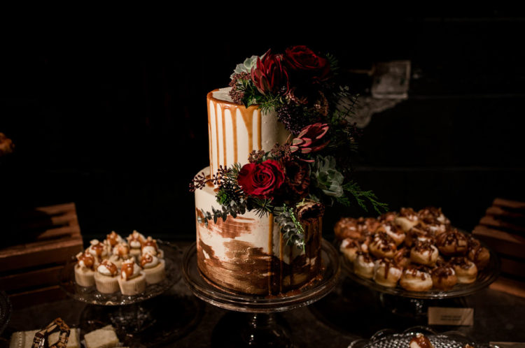 The wedding cake was done with gold leaf, caramel drip and fresh blooms and greenery