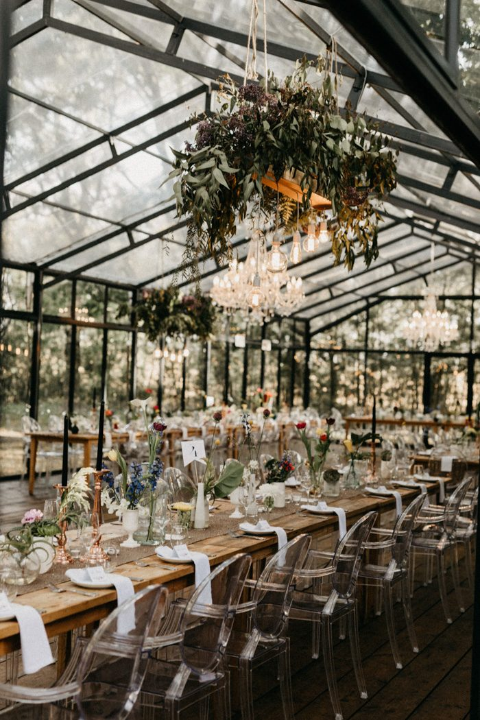 The wedding venue was done with chic greenery chandeliers, clear chairs, mismatching vases with flowers