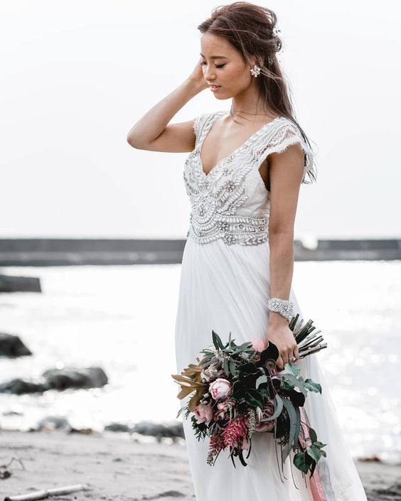 a boho glam wedding gown with an embellished bodice, a V-neckline and cap sleeves plus a matching bracelet