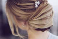 10 a textural low chignon hairstyle with a bump, bangs and a rhinestone hairpiece for an accent