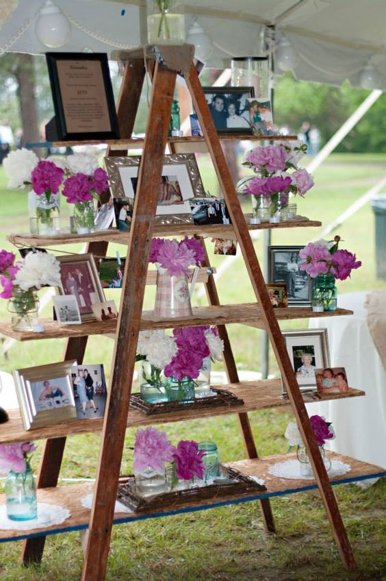 a wedding display with photos, flowers and frames can be a nice wedidng decoration for any space