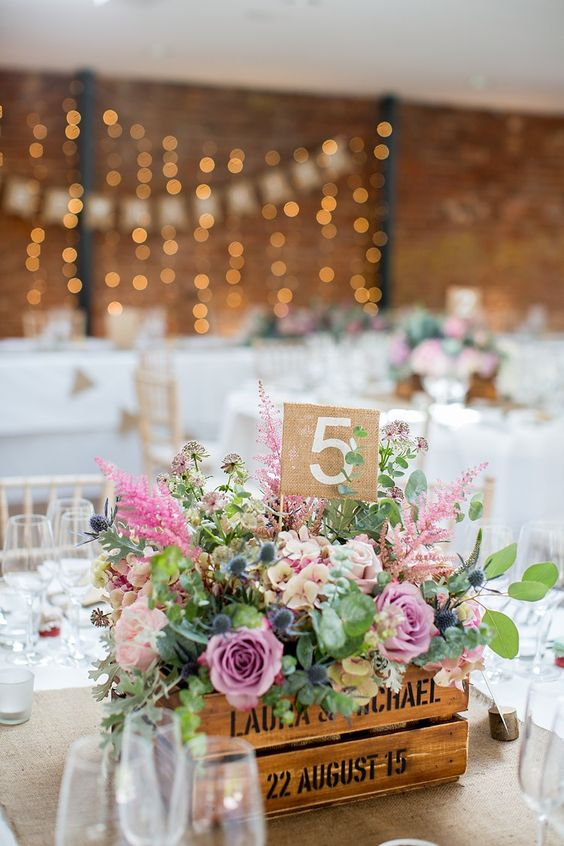 a stenciled crate with lush florals and greenery plus a table number will be a nice wedding centerpiece