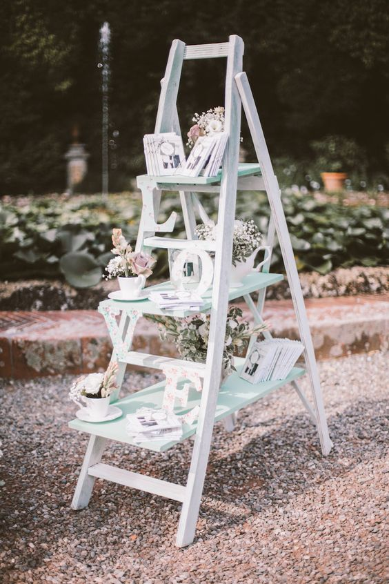 a whitewashed ladder with letters and flower arrangements in teacups for a vintage wedding