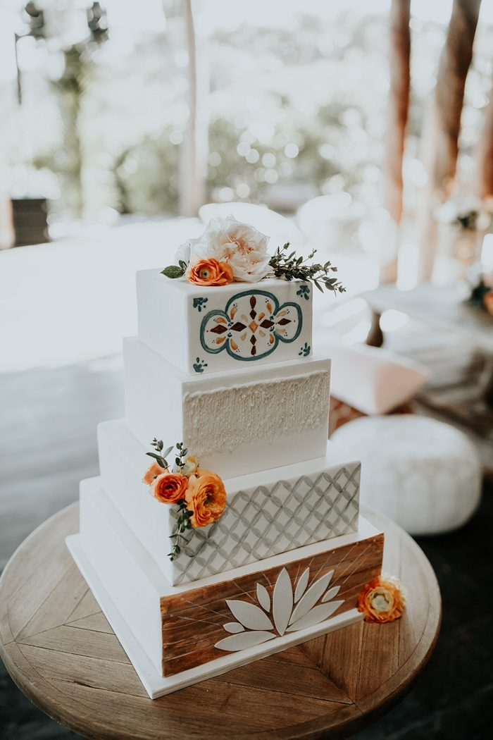 The wedding cake had painted and textural tiers and flowers on top