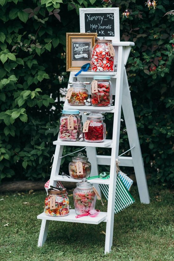 a candy table of a ladder and jars with all kinds of candies and frames