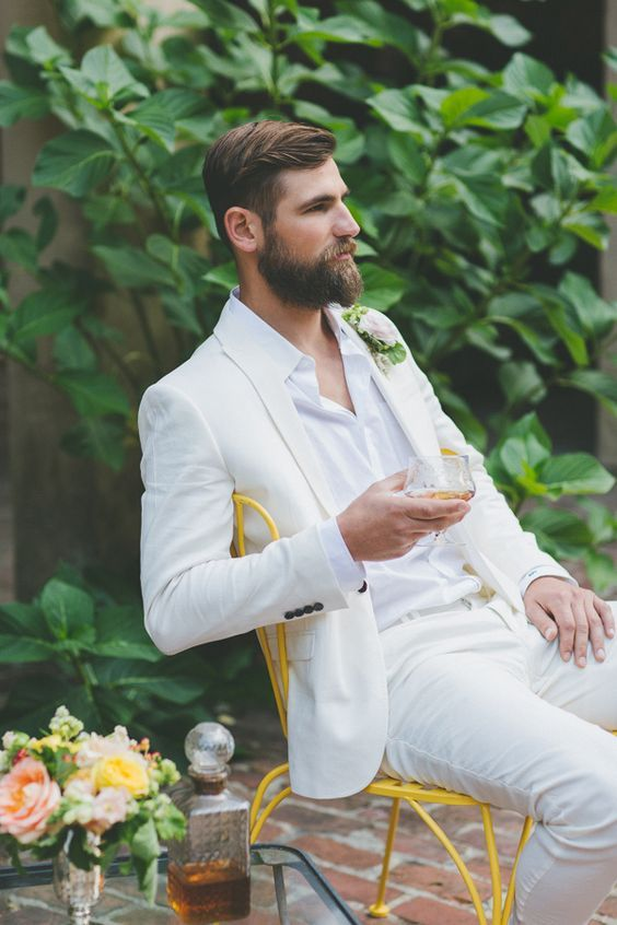 a white suit and shirt plus a blush boutonniere for a relaxed summer groom look