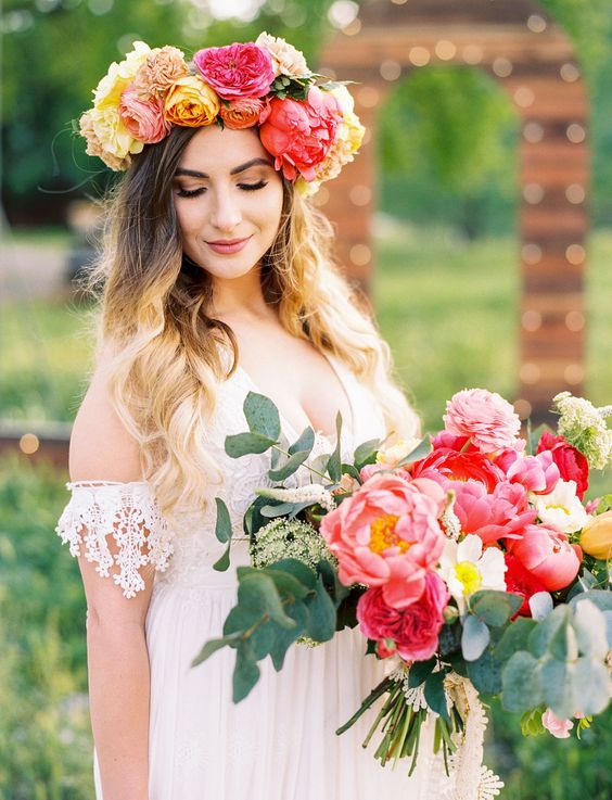 a colorful large flower crown in red, yellow and orange and a matching wedding bouquet