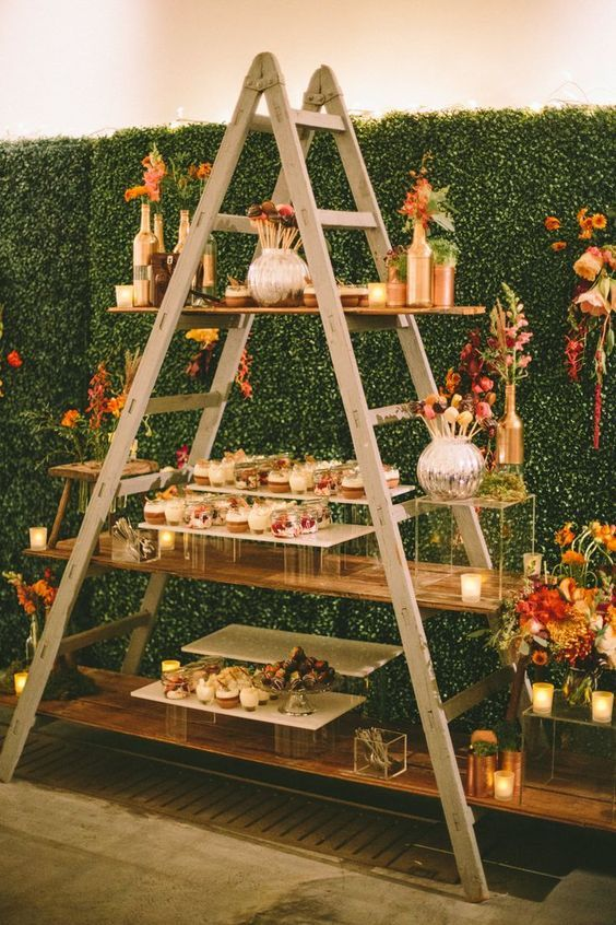 a dessert table designed of a ladder and shelves plus clear glass stands and gold vases and pots for a glam feel