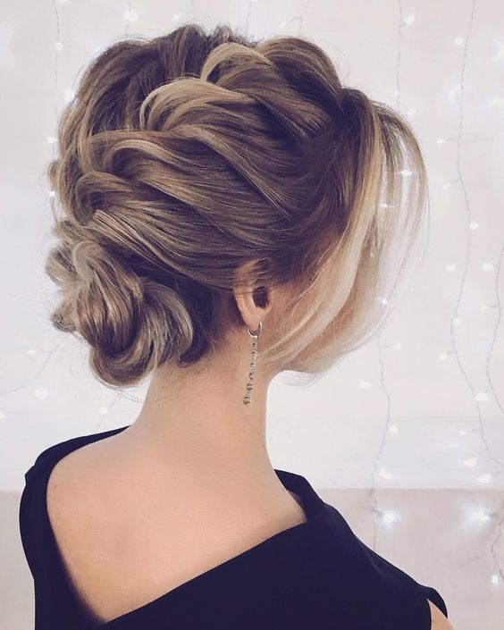 a voluminous braided updo with some locks around the face looks super elegant