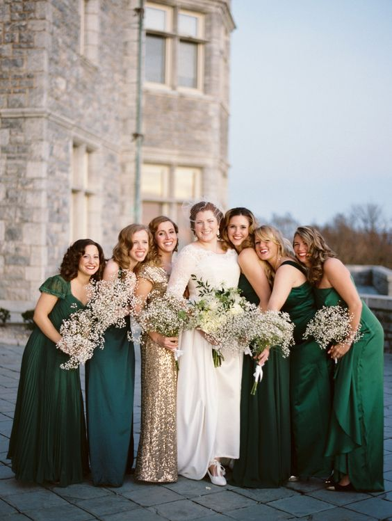 bridesmaids wearing emerald dresses and a gold sequin gown for the maid of honor