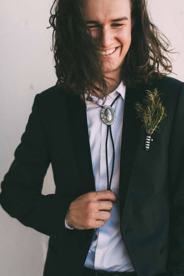 a black suit, a white shirt and a bolo tie for an effortlessly chic boho groom's look