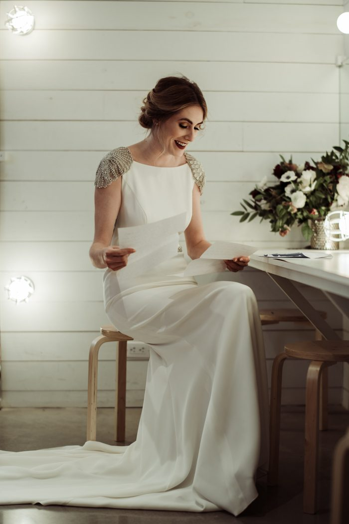 a fantastic plain fitting wedding dress with embellished cap sleeves, a train and an open back
