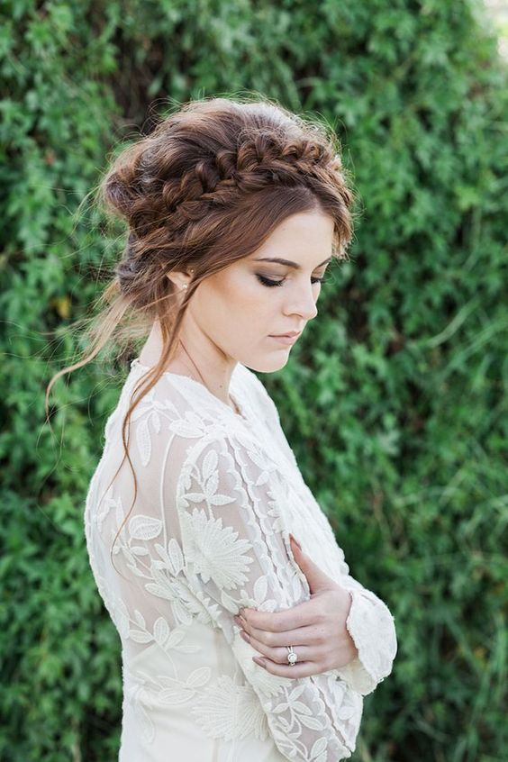 a messy updo with a loose halo braid on top and some locks down for a boho bride