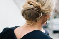 15 a creative low chignon hairstyle with some twists and curled bangs for a chic look