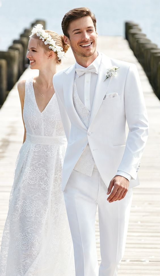 a gorgeous white three-piece suit with a patterned vest, a white shirt, a white bow tie and a white boutonniere