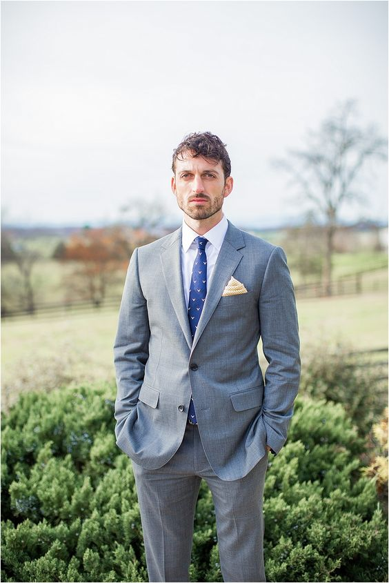 a grey suit is spruced up with a bold blue printed tie for a brighter look and a more modern feel