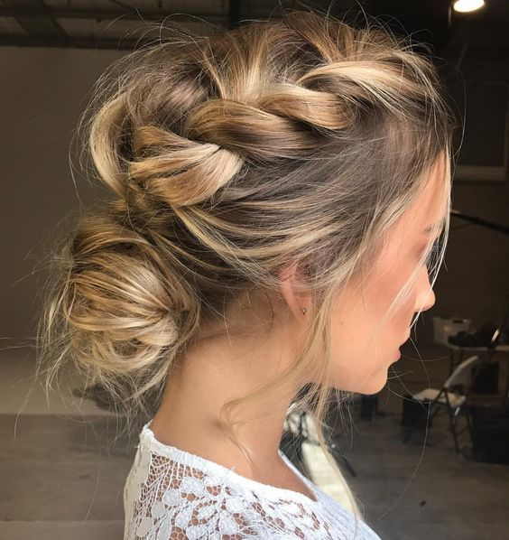 a messy braided updo with a low bun and locks down for a casual modenr bride