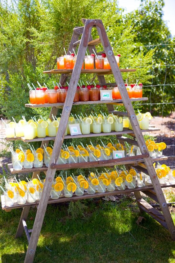 a wedding drink station is arranged with a ladder and large shelves for holding all the drinks