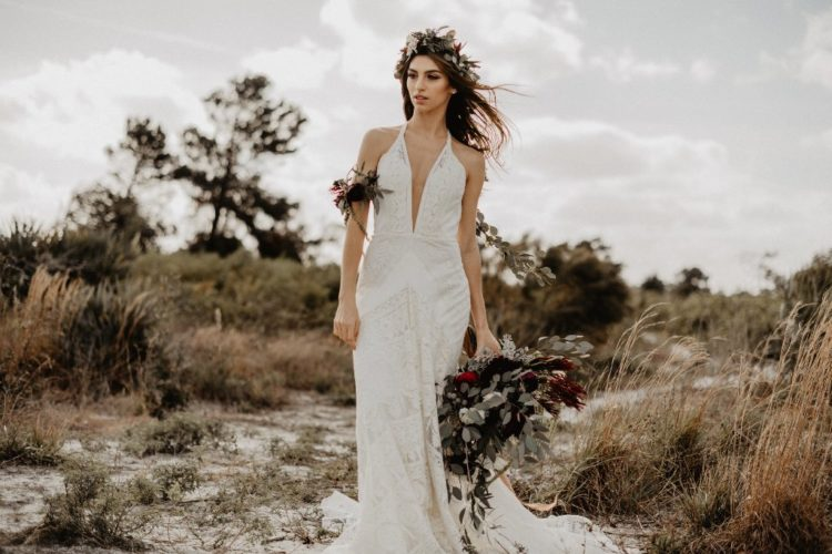 Comic Coralee sheath lace wedding gown with a plunging neckline, spaghetti straps and a strappy back