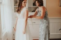 16 a grey sheath dress with thick straps and silver floral embellishments plus neutral shoes