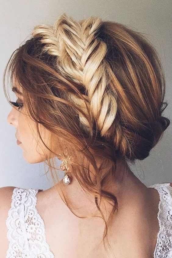 a messy and wavy updo with a large fishtail braid in the center and locks down