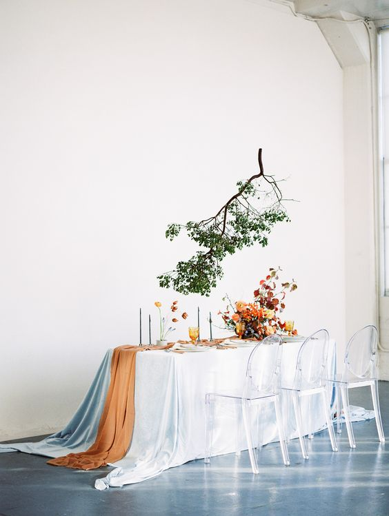 a modern tablescape done in orange and burgundy plus light blue and a green branch over the table