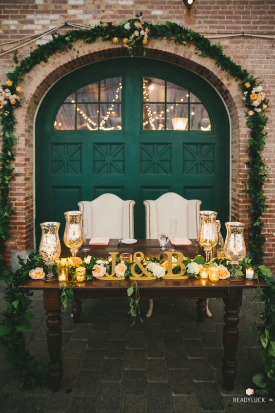 a wow sweetheart table with gold and greeneyr, candles and an emerald door behind it