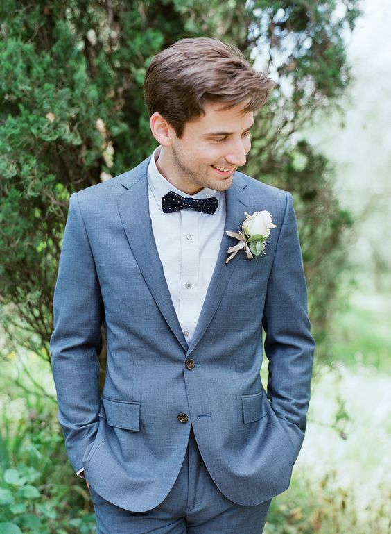 a grey wedding suit, a white shirt, a navy polka dot bow tie for an elegant feel
