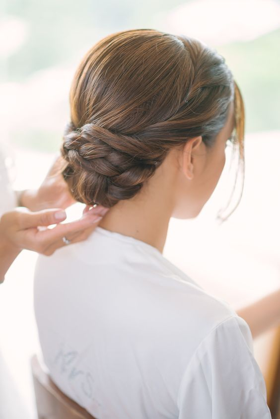 a low twisted and braided bun with a sleek top looks very elegant and chic